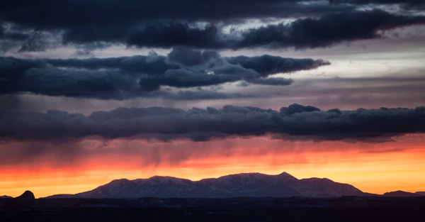 Rain falls on mountains in Canyonlands: Islands In the Sky National Park at sunset on Friday, Feb. 22, 2013.