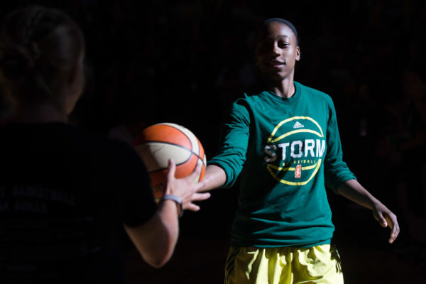 Jewell Loyd hands a ball off to a lucky fan during player introductions before a game against the Dallas Wings on July 28, 2017. (Neil Enns/Storm Photos)