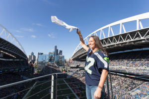 Sue Bird hypes the crowd by waving a 12th Man towel before kickoff at the Seattle Seahawks game on August 25, 2017. (Neil Enns/Storm Photos)